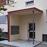 Haustürvordach aus Stahlbeton mit seitlichem Sicht- und Windschutzelement