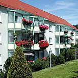 Systembalkone aus Stahl viereckig mit weißer Stahlrahmenkonstruktion und Sichtschutzblende. Typ Elegance - Sechseckform mit Überdachung