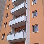 Betonbalkon mit weißem Glasgeländer