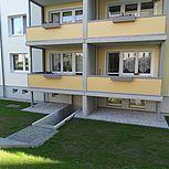 Betonbalkon mit gelben Geländer und Blumenkasten