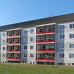Rechteckige Balkonerweiterung aus Aluminium mit roten Trespaplatten und Betondach