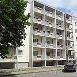 Betonbalkon mit grau-gelben Geländer an fünfstöckigem Wohnhaus