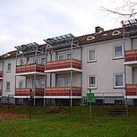 Systembalkone aus Stahl mit orangener Stahlrahmenkonstruktion mit Schichtstoffplattenfüllung