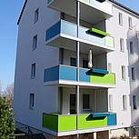 Betonbalkon als Vorstellbalkone mit grün-blauen Geländer