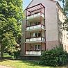 Rechteckiger Stahl- und Aluminiumbalkon mit Trespaplatten-Geländer und roten Stützen ohne Sichtschutz